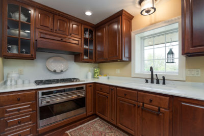 Cherry Cabinets and White Countertops in a Kitchen
