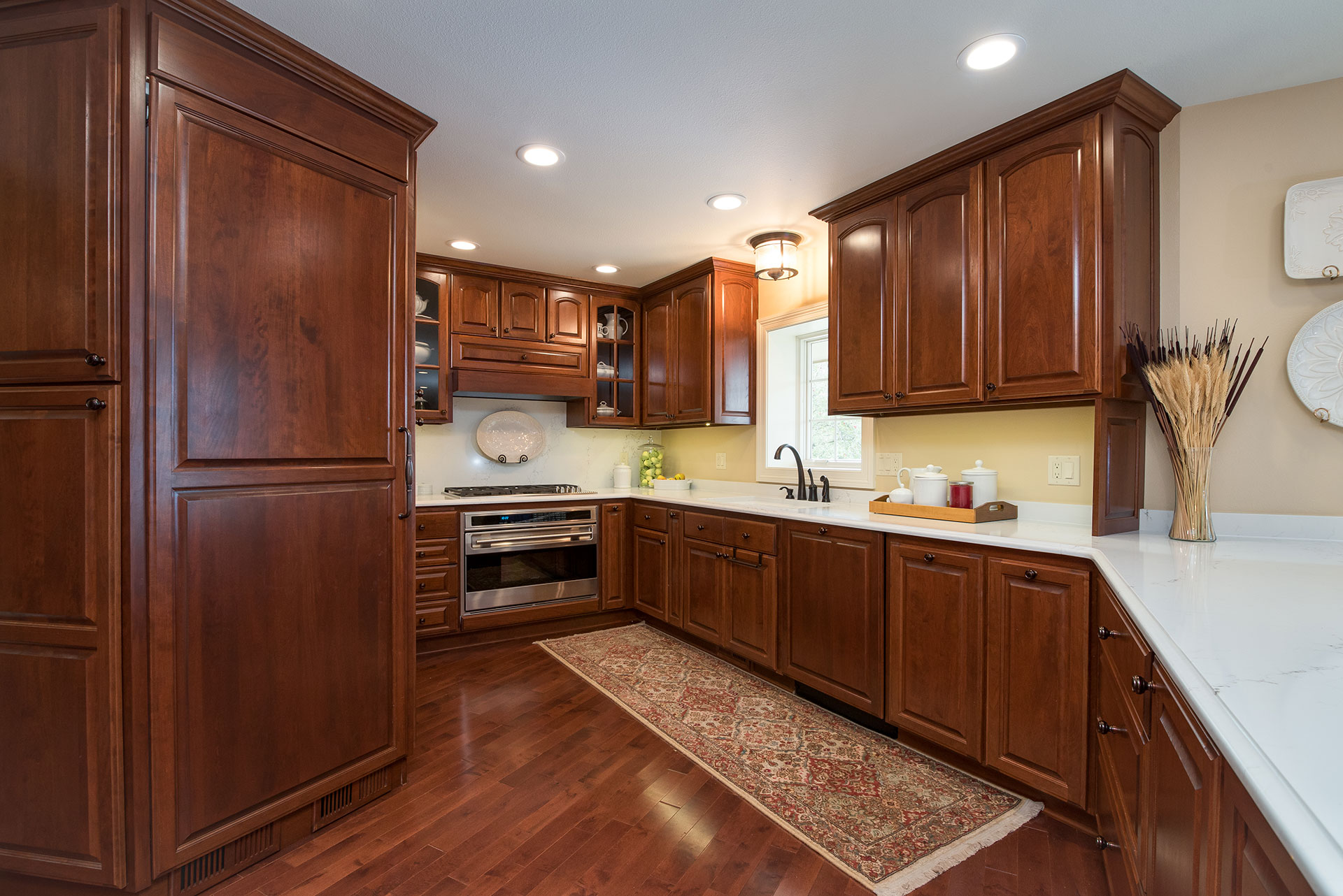 Cherry Cabinets And White Countertops In A Kitchen Nuwood Cabinets